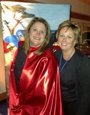 (left)  Jennifer Gabales, CAHSAH Policy Director wearing her Superwoman Cape with (right) Denise Altomare, CAHSAH Chair, Board of Directors (Note:  In the background a fabulous Superheroes painting by Mary Adorno, CAHSAH Legislative Assistant.)