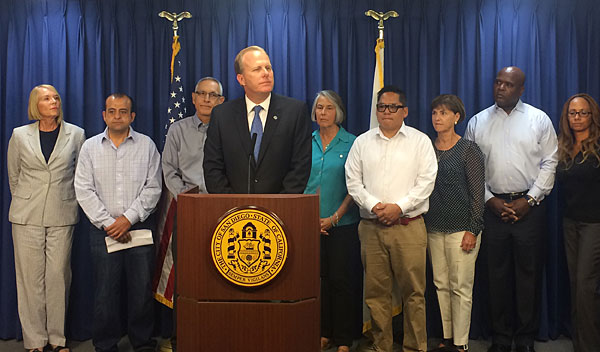 San Diego Mayor Faulconer stands up against the current initiative to increase Minimim Wage in San Diego at his press conference this morning at City Hall. Pictured behind him (left) Laurie Edwards-Tate  President At Your Home Familycare joins other concerned members of the Small Business Coalition.
