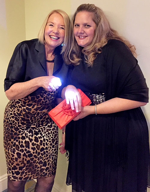 Laurie Edwards-Tate with Karen Hooper, VP, of the Pacific Coast Chapter of the the MS Society brightened by the light of their gala glow rings.